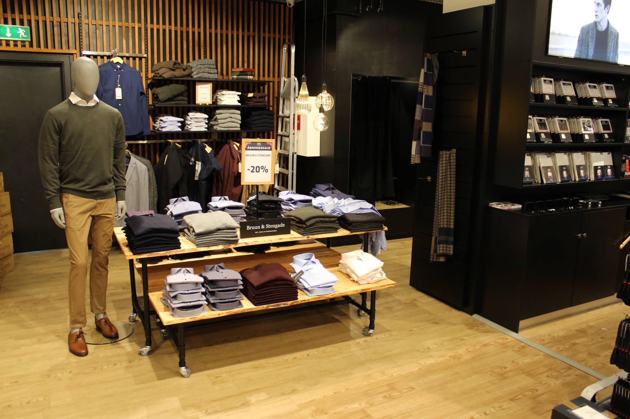 Trendy indrettet herrebutik med nøddefarvet lamelvæg