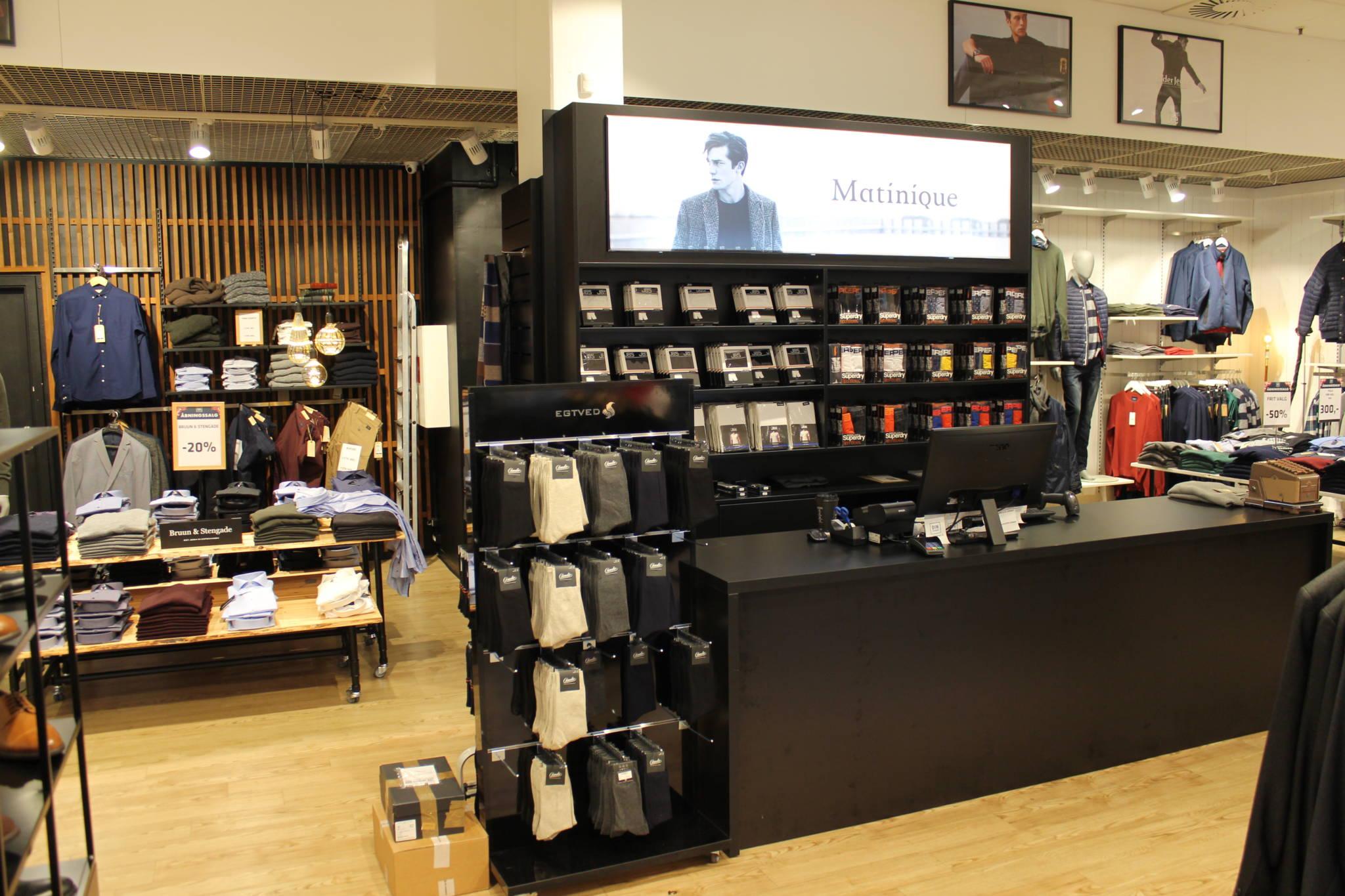 Trendy indrettet herrebutik med nøddefarvet lamel væg og sort diskområde